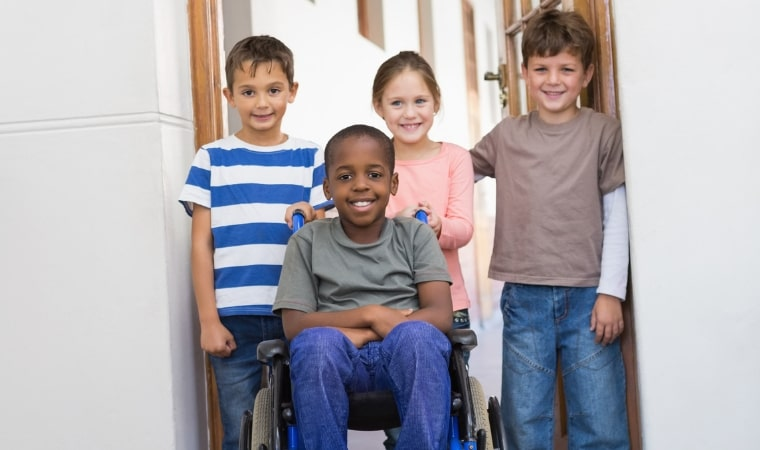 boy in wheelchair and children ready to read puberty books on disability