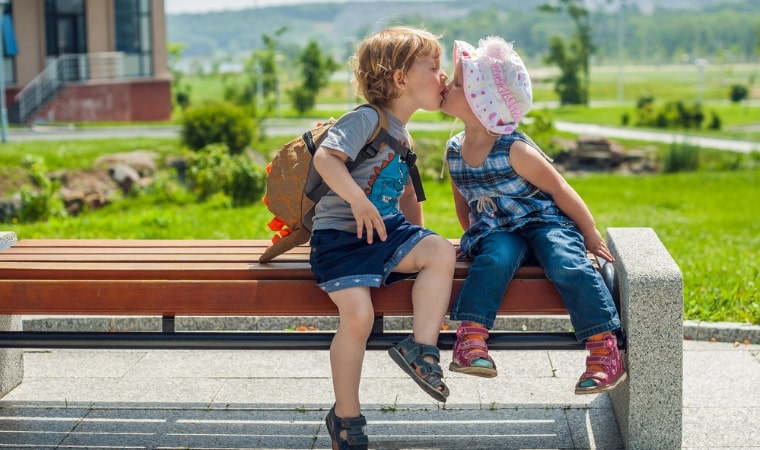 childhood kiss between 2 young children for a teachable moment
