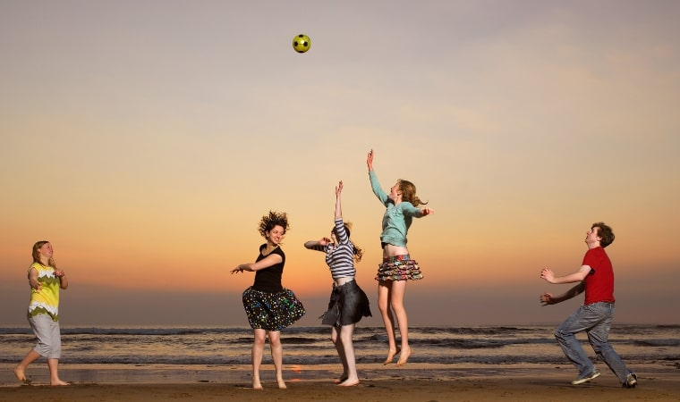 group of 13 year olds playing with a ball at the beach