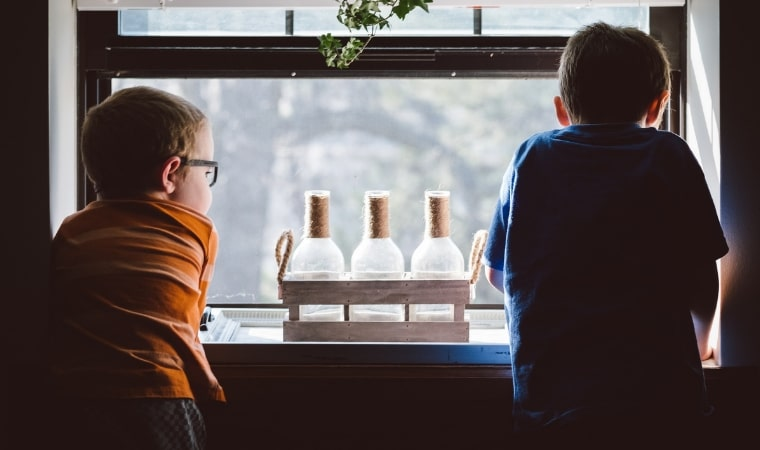 2 boys standing in front of a window