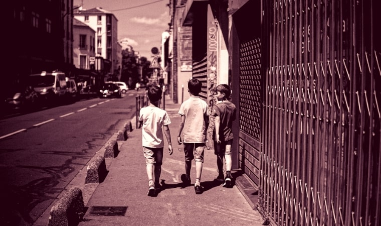3 boys walking down a street